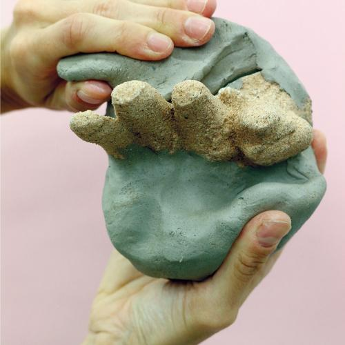 Two hands holding a sculpture made of green clay with stones sticking out