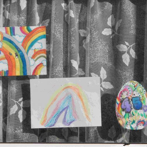 Two rainbow paintings and a brightly coloured Easter egg in a window