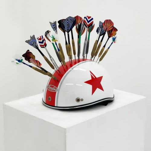 Untitled (Helmet and Darts), darts on top of a white helmet with a single red stripe, side view