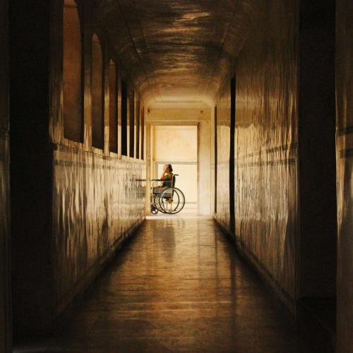 Temporary II, photograph of a corridor with person in a wheelchair in the background