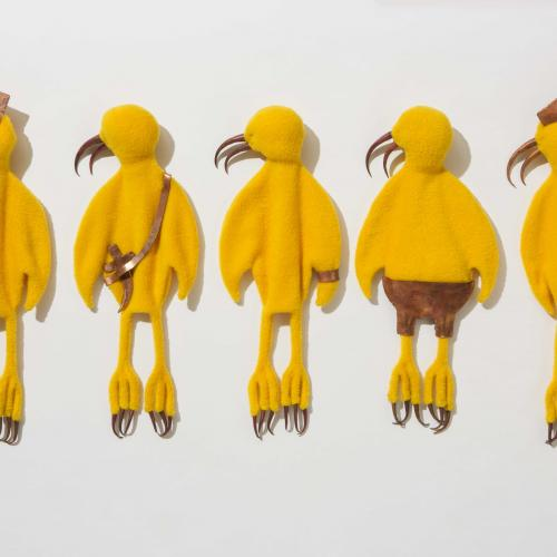 Yellow Birds, five yellow cartoon-like birds made of fleece and laid down next to one another with their head facing left, each featuring a fabric accessory such as hats, shorts, a bag, and hair tied in a bun