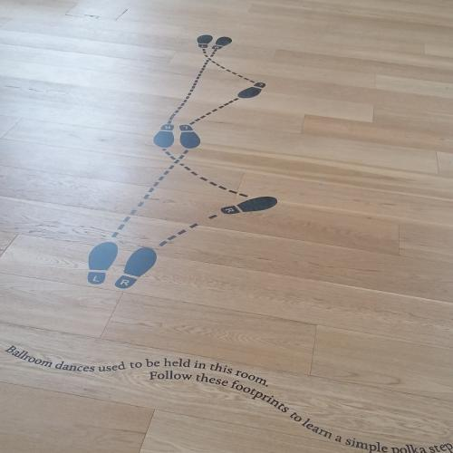 Footsteps marking the positions for a dance in black on the pale Assembly Room floor