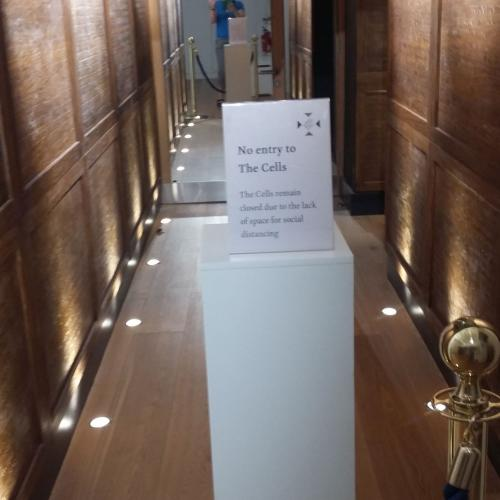 A plinth blocking the corridor to the cells with a sign explaining this is because of Covid restrictions. The Honours Boards are behind the blocked off plinth.