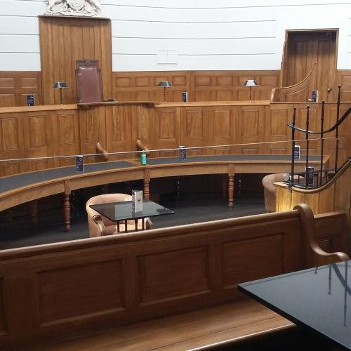 The Courtroom with tables and chairs arranged with more space between them and fewer tables