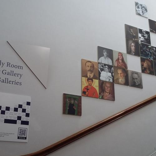 Display of portraits of people on the wall of the Grand Staircase with an information panel at the bottom