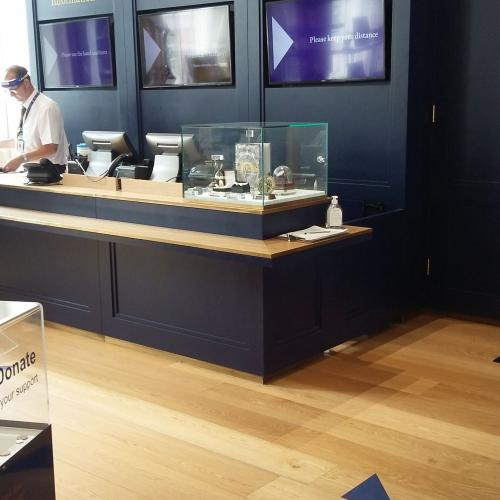 The museum front desk with a staff member behind it wearing a visor