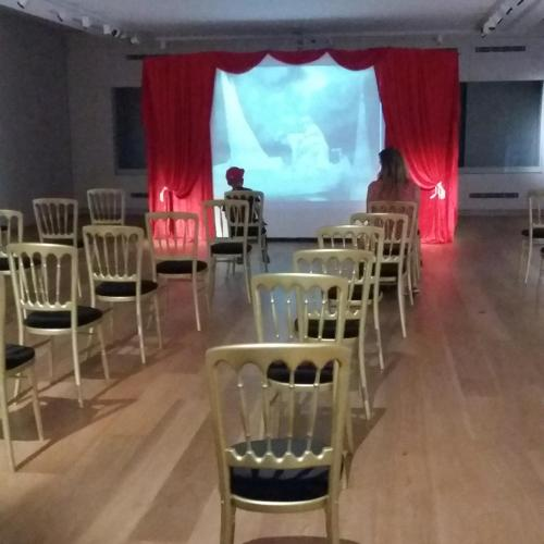 Cinema set out in the Weston Gallery with socially distanced seating. The screen is at the far end of the gallery as you enter.