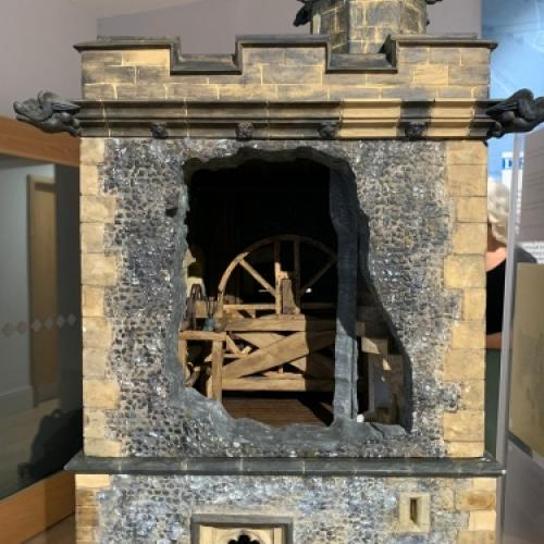 A close up of the bell mechanism in the scale model of the clock tower