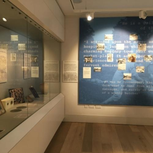 Exhibition gallery showing a case and a wall covered in blue text