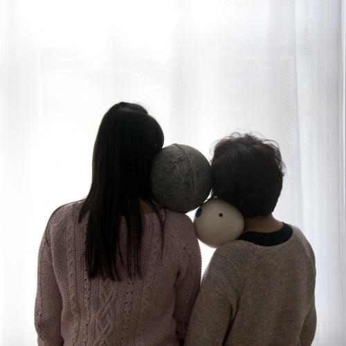 Two Buoys Two Voids, photograph showing the back of two people standing close in front of a bright white screen and holding two buoys on their shoulder.
