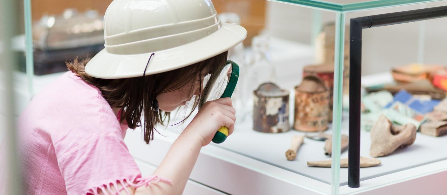 Child in explorer hat looking at museum objects in a glass case with a magnifying glass
