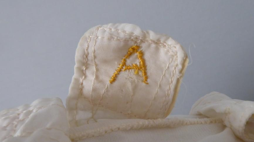 "Photo of detail from John Allam's white inner helmet liner with embroidered yellow ""A"""