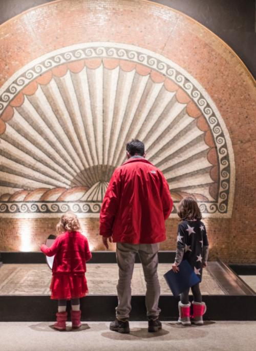 Photo of visitors admiring the shell mosaic at Verulamium Museum