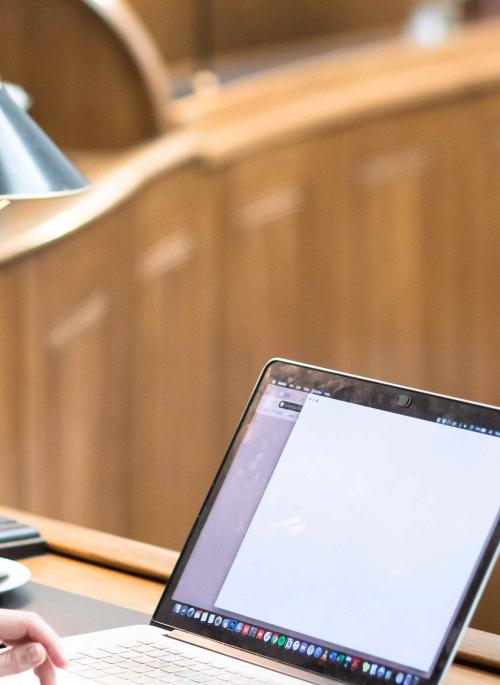 A woman looking at her laptop in the St Albans Museum + Gallery Court Room