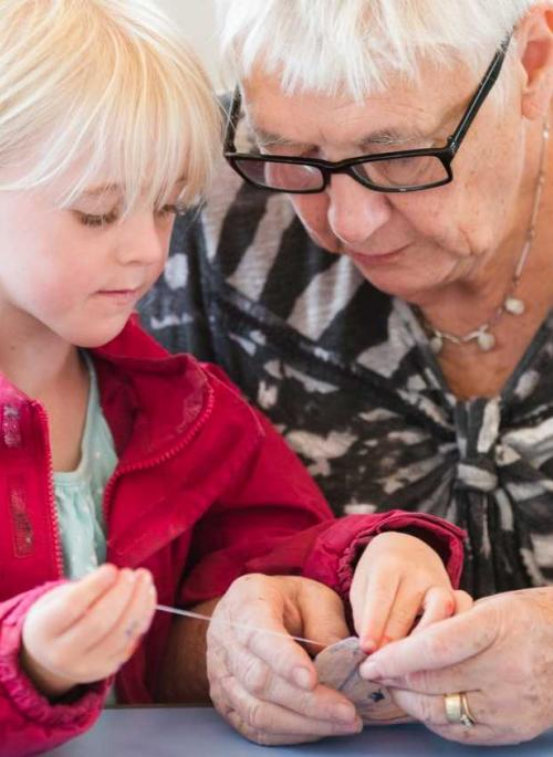 child making a craft activity with grandmother